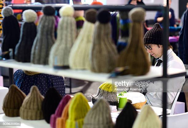 An exhibitor from Finland knits a hat during the Greenshowroom trade show during the MercedesBenz Fashion Week Berlin Autumn/Winter 2016 at...