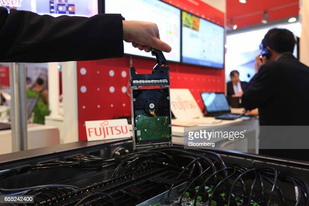 An exhibitor lifts a computer unit from a liquid cooled server rack sits on display in the Fujitsu Ltd pavilion at the CeBIT 2017 tech fair in...