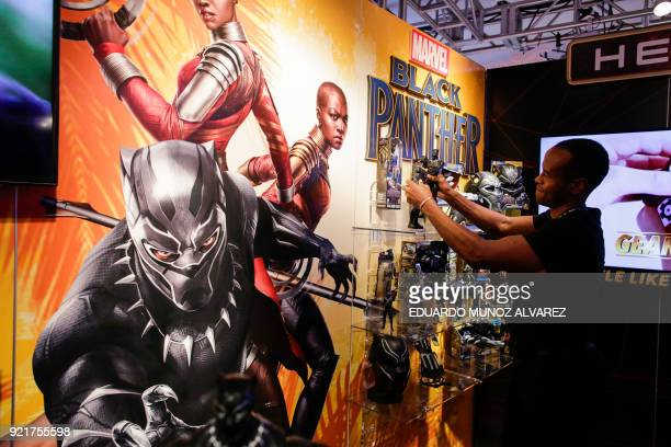An exhibitor organizes 'Black Panther' items at the Hasbro showroom during the annual New York Toy Fair on February 20 in New York Panther claws...