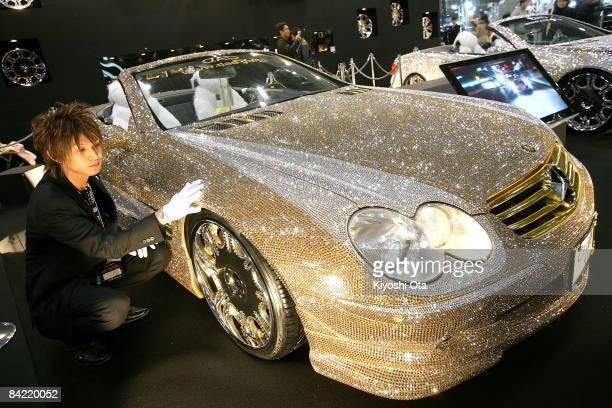 An exhibitor polishes a 'Luxury Crystal Benz' the customized MercedesBenz SL600 with 300000 Swarovski crystals displayed at a booth at Tokyo Auto...