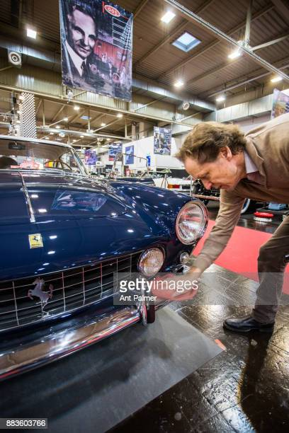 An exhibitor polishes an classic Ferrari before the opening of the Essen Motor Show on December 1 2017 in Essen Germany The Essen Motor Show is...