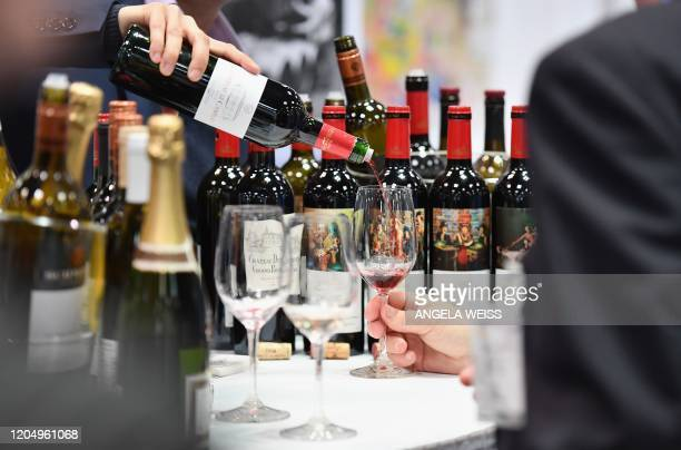 An exhibitor pours red wine during the Vinexpo at Javits Center on March 2, 2020 in New York City. - The wine business dodged a bullet last month...