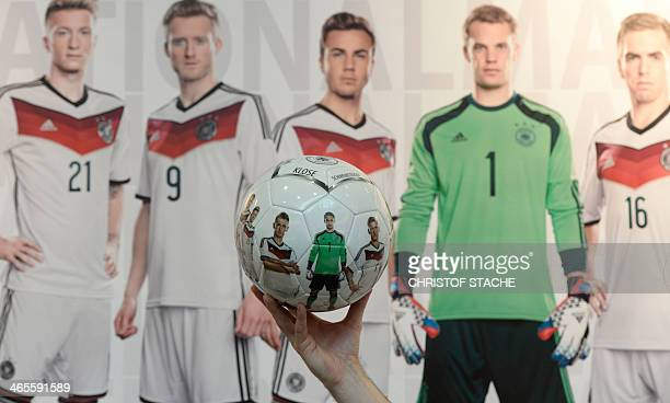 An exhibitor presents a ball with pictures of German Bundesliga first division football team players at the International Toy Fair in Nuremberg...