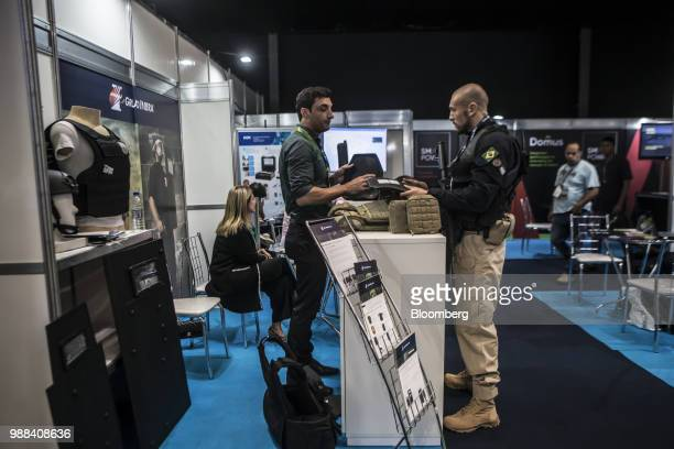 An exhibitor shows an attendee armor from a bulletproof vest during the Rio International Defense Exhibition in Rio de Janeiro Brazil on Friday June...
