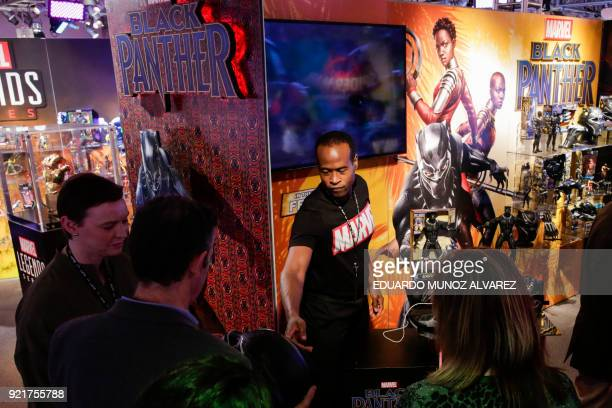 "An exhibitor shows ""Black Panther"" items to attendees at the Hasbro showroom during the annual New York Toy Fair, on February 20 in New York. Panther..."