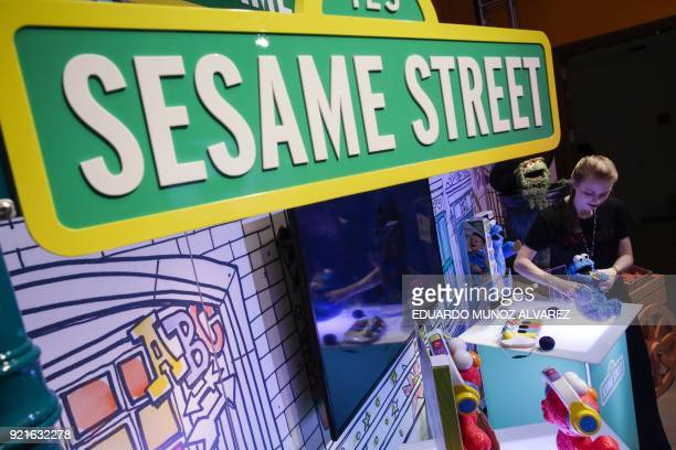 An exhibitor shows Sesame Street toys at their booth during the annual New York Toy Fair on February 20 in New York / AFP PHOTO / EDUARDO MUNOZ...