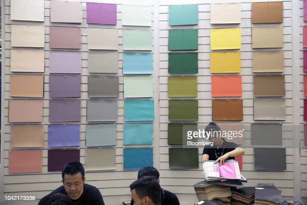An exhibitor stands in front of a display of product samples at the All China Leather Exhibition in Shanghai China on Thursday Aug 30 2018 As the...