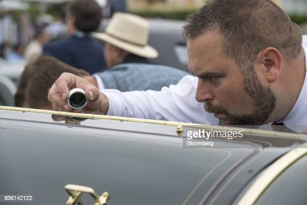 An exhibitor touches up paint on the hood of a 1910 Thomas Flyer Model K 670 Flyabout during the 2017 Pebble Beach Concours d'Elegance in Pebble...