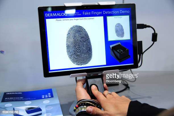 An exhibitor uses a fingerprint scanning device as part of a fake finger detection demonstration at the Dermalog Identification Systems GmbH pavilion...