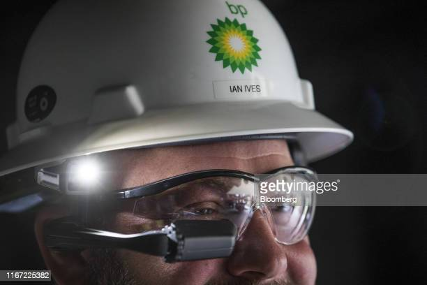 An exhibitor wears a maintenance helmet with a headset display at a BP Plc immersive technology event at the company's International Centre for...