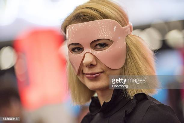 An exhibitor wears a Wired Beauty Mapo connected beauty mask during the South By Southwest Interactive Festival at the Austin Convention Center in...