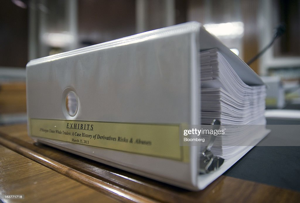 An exhibits binder for the Senate Permanent Subcommittee on Investigations hearing titled JPMorgan Chase Whale Trades: A Case History of Derivatives Risks and Abuses sits on a witness table the hearing room in Washington, D.C., U.S., on Friday, March 15, 2013. JPMorgan Chase & Co., the biggest U.S. bank by assets, compensated chief investment office traders in a way that encouraged risk-taking before the unit amassed losses exceeding $6.2 billion, a Senate committee said. Photographer: Andrew Harrer/Bloomberg via Getty Images