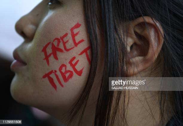 TOPSHOT An exiled Tibetan activist face is painted with the slogan Free Tibet during a protest marking the 60th anniversary of the 1959 Tibetan...