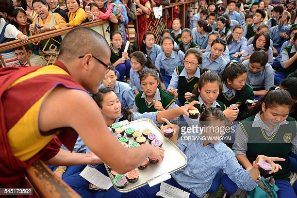 An exiled Tibetan monk distributes cupcakes to school children to mark the Dalai Lama's 81st birthday in McLeod Ganj on July 6 2016 / AFP / Lobsang...