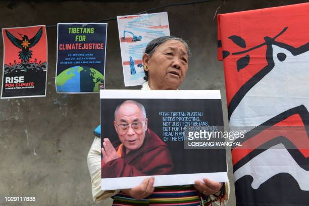 An exiled Tibetan woman holds a portrait of Tibetan spiritual leader the Dalai Lama at a Rise for Climate event in McLeod Ganj in India's Himachal...
