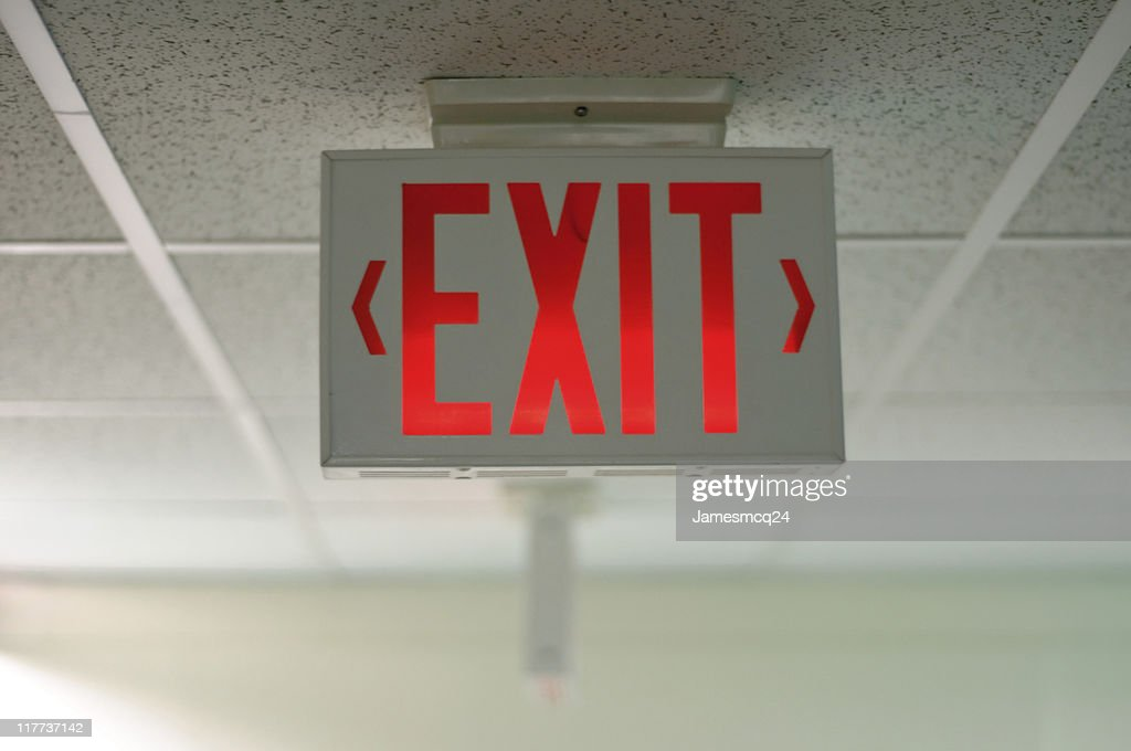 An exit sign hanging from a ceiling : Stock Photo