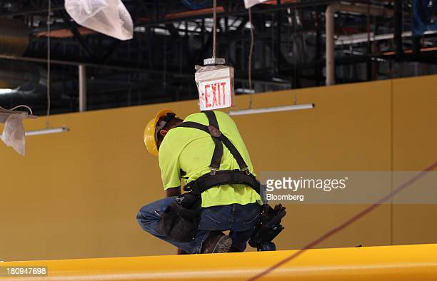 """An """"Exit"""" sign hangs over a worker inside a new Whole Foods Market Inc. Store under construction in Park Ridge, Illinois, U.S., on Tuesday, Sept. 17,..."""