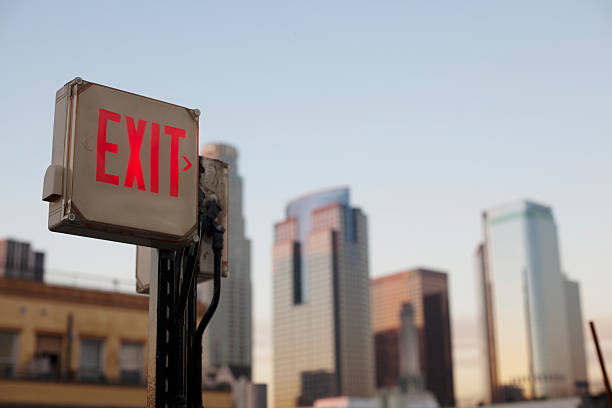 an exit sign in fron of a big city skyline