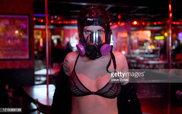 An exotic dancer poses in her respirator in the Lucky Devil as she waits to go out on a delivery on March 27 2020 in Portland Oregon The local...