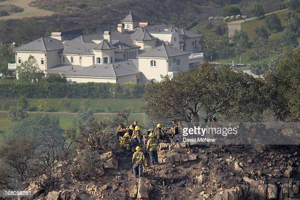 An expansive luxury home sits in the distance as firefighters take a break while constructing firelines by hand at the Springs fire on May 4 2013...