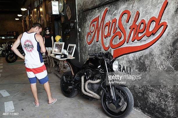 An expatriate looks at an old motorcycle parked as a display in ManShed Cafe Sanur The ManShed cafe in Sanur Bali is themed on an old style garage...
