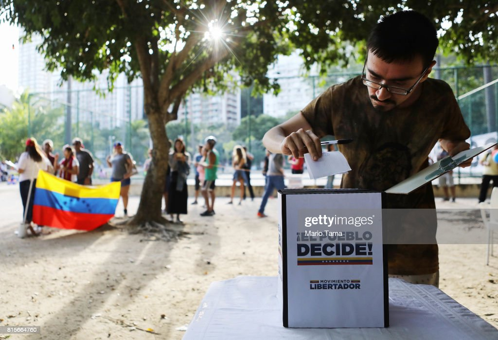 An expatriate Venezuelan casts his ballot as others wait on line during an unofficial referendum, or plebiscite, held by Venezuela's opposition against Venezuela's President Nicolas Maduro's government on July 16, 2017 in Rio de Janeiro, Brazil. Voting was conducted across 2,000 polling centers in Venezuela and in more than 80 countries around the world amidst a severe crisis in Venezuela.