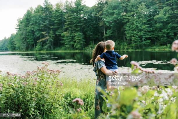 an expecting mother holding her toddler son in her arms - nature reserve foto e immagini stock