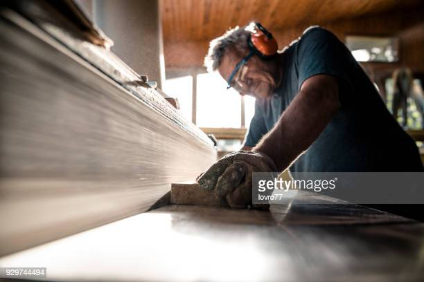 An experienced carpenter shapes the timber on a grinding wheel