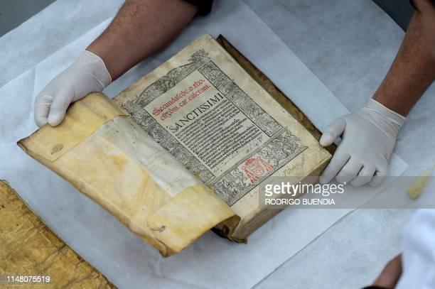 An expert checks an incunable at the Fray Ignacio de Quezada library, at the Convent of Santo Domingo de Guzman, in Quito on May 27, 2019. -...