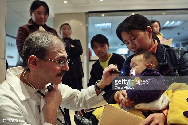 CHINA An expert gives examines a child suffering from cleft lip and palate during a campaign held by the Operation Smile International at the Nanjing...