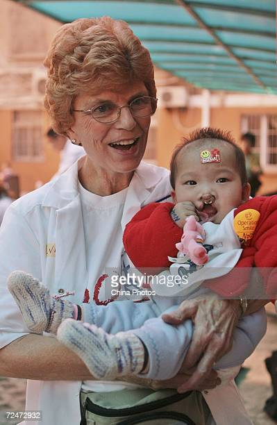 An expert holds a Chinese child suffering from cleft lip and palate during a campaign held by the Operation Smile International at the Nanjing Gulou...
