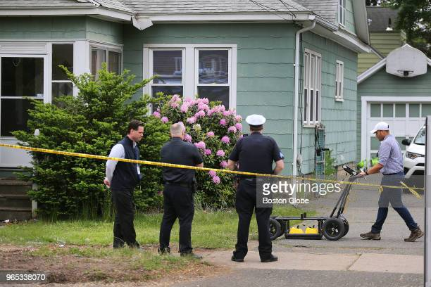An expert in ground penetrating radar pushes a device across the front yard as investigators continue to work at a crime scene in Springfield MA on...