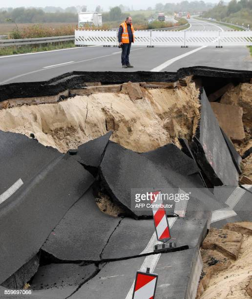 An expert inspects the cutoff section of the A20 motorway at the site of an unexplained landslide near Tribsees northern Germany on October 10 2017...