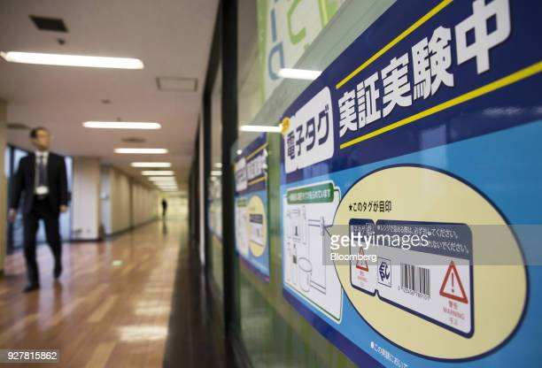 An explanation of radiofrequency identification tags is displayed outside a FamilyMart UNY Holdings Co FamilyMart convenience store in Tokyo Japan on...