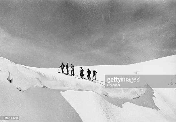 An exploratory party led by Alf Engen, forest officers, and citizens from Twin Falls, stops above a snow cornice on Minidoka's Magic Mountain,...