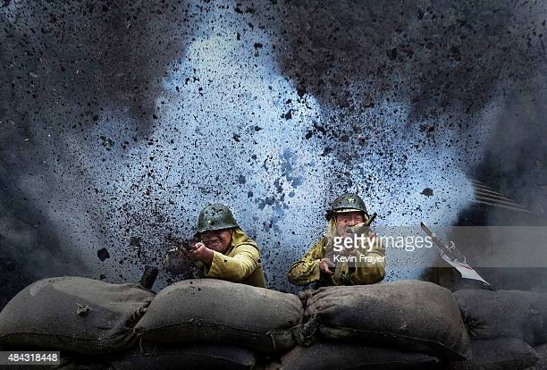 An explosion goes off as Chinese actors playing Japanese soldiers are are filmed in a battle scene during filming of the series 'The Last Noble' set...