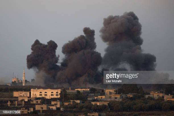 An explosion in the Syrian side of the IsraeliSyrian border is seen from the Israeli Golan Heights on July 23 2018 in Sayda al Golan Syria Russian...