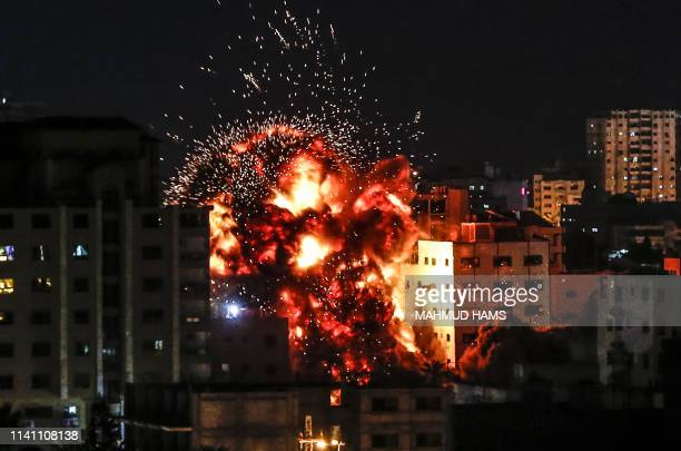 TOPSHOT An explosion is pictured among buildings during an Israeli airstike on Gaza City on May 4 2019 Gaza militants fired a barrage of rockets at...