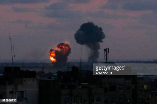 TOPSHOT An explosion is seen at Rafah town in the southern Gaza Strip after an airstrike by Israeli forces on June 20 2018 Israeli fighter jets hit...