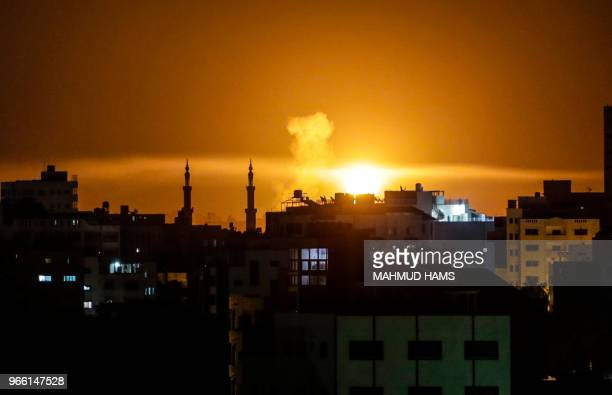 TOPSHOT An explosion is seen in Gaza City after an airstrike by Israeli forces late on June 2 2018 Israeli aircraft pounded over a dozen militant...