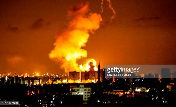 TOPSHOT An explosion is seen in Gaza City after an airstrike by Israeli forces on June 18 2018 Israeli aircraft pounded over a dozen militant targets...