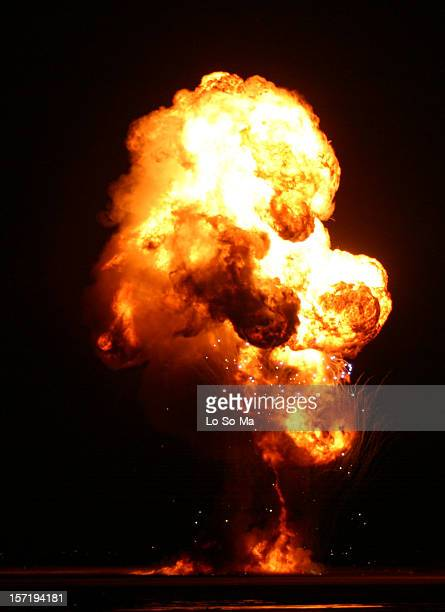 an explosion lit up the darkness with red and yellow flames - mushroom cloud stock pictures, royalty-free photos & images