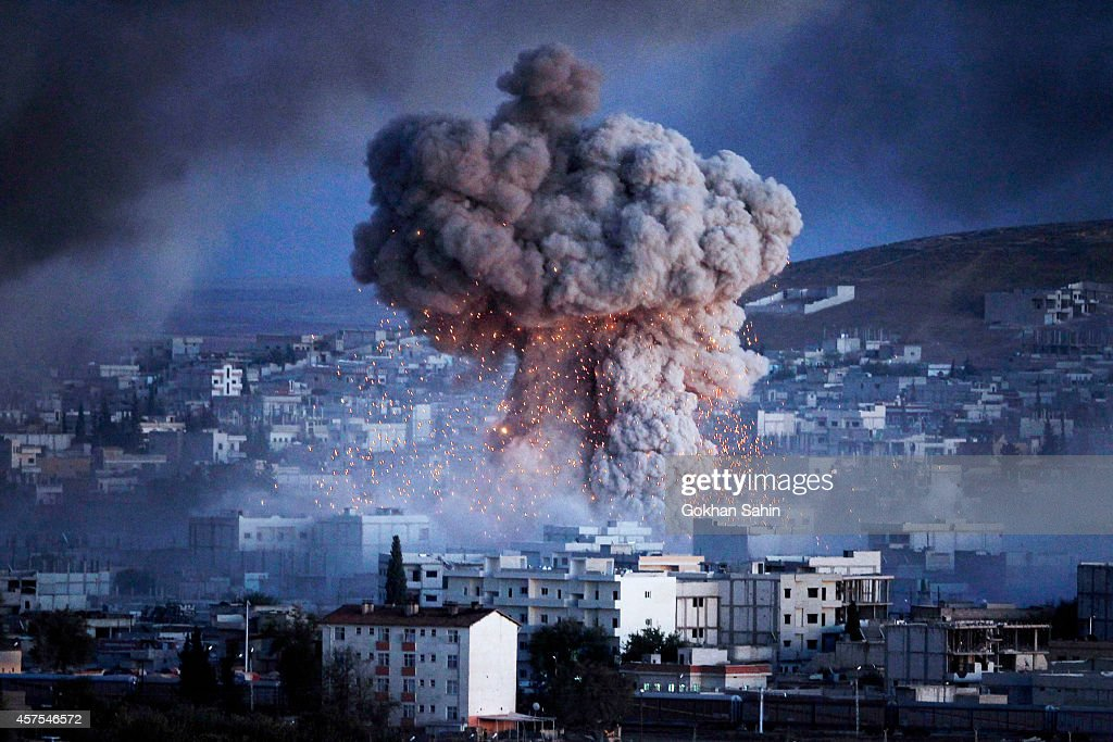 An explosion rocks Syrian city of Kobani during a reported suicide car bomb attack by the militants of Islamic State (ISIS) group on a People's Protection Unit (YPG) position in the city center of Kobani, as seen from the outskirts of Suruc, on the Turkey-Syria border, October 20, 2014 in Sanliurfa province, Turkey. According to Foreign Minister Mevlut Cavusoglu, Turkey will reportedly allow Iraqi Kurdish fighters to cross the Syrian border to fight Islamic State (IS) militants in the Syrian city of Kobani while the United States has sent planes to drop weapons, ammunition and medical supplies to Syrian Kurdish fighters around Kobani.