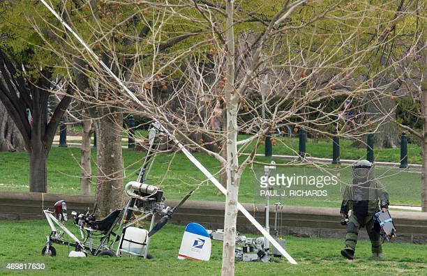 An Explosive Ordnance Disposal Technician and a robotic police device check a mini helicopter or gyrocopter that landed on the US Capitol South Lawn...