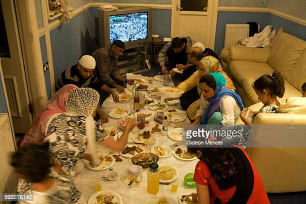 An extended Muslim family gather for an evening meal at the end of a day of fasting during the month of Ramadan They are seated on the floor because...