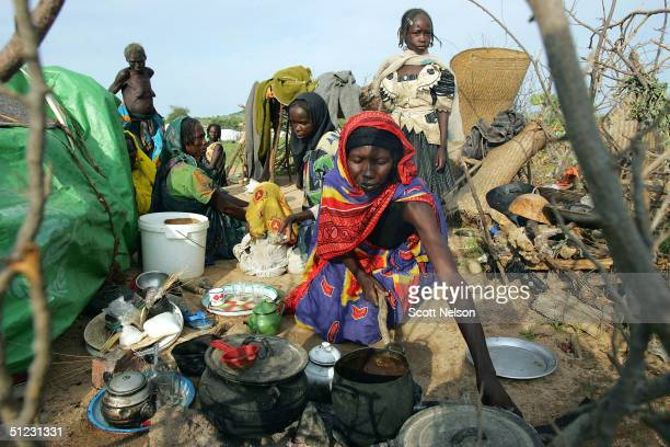 An extended refugee family from the Darfur region of Sudan prepares a modest breakfast by their tent August 28 2004 in the spontaneous overflow camp...