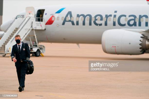 An exterior view of an American Airlines B737 MAX airplane is seen as a man walks at Dallas-Forth Worth International Airport in Dallas, Texas on...