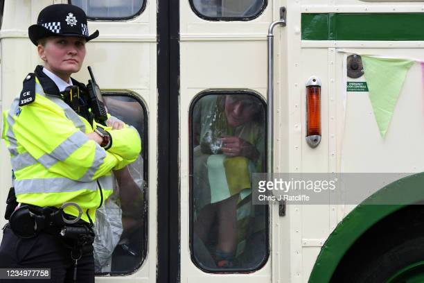 An Extinction Rebellion activist glues her hand to an old bus which is blocking the road by London Bridge as part of the Impossible Rebellion 2021...