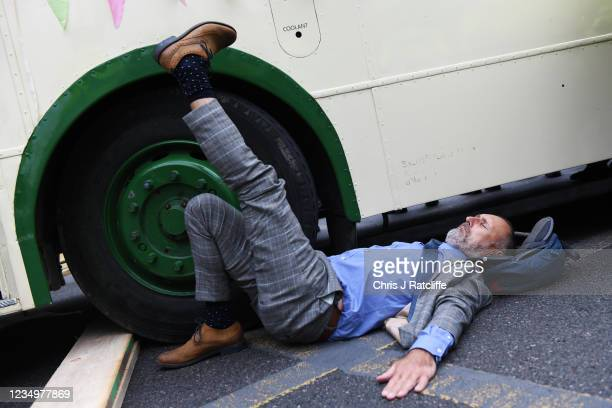 An Extinction Rebellion activist glues his hands to the ground next to an old bus which is blocking the road by London Bridge as part of the...