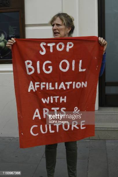 An Extinction Rebellion activist holds a banner outside the Royal Opera House main entrance during a protest in London Environmental Activists from...